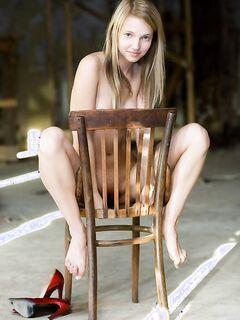 Тощая блонда позирует оголенной на стуле