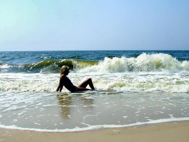 Сексуальная блондинка прогуливается топлес по пляжу