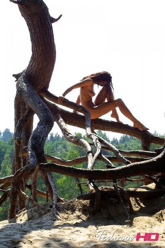 Лесная нимфа отдыхает голой на дереве