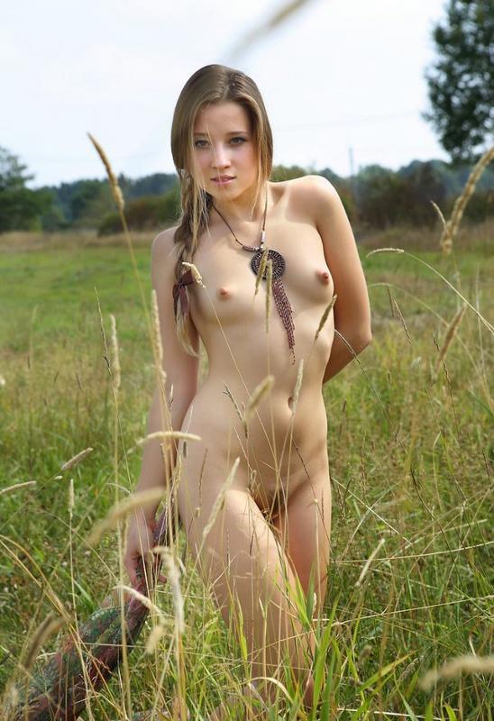 Худощавая девушка расставила ноги на зеленом лугу